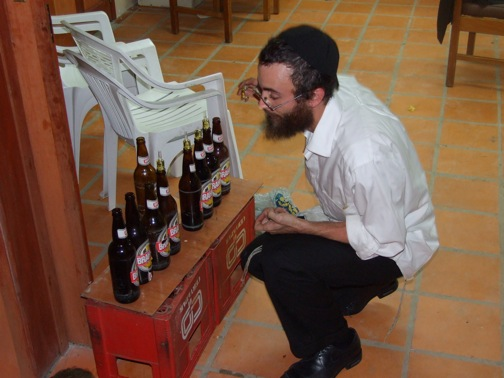 The Chabad shaliach lighting a makeshift menorah in the Chabad of Asuncion, Paraguay